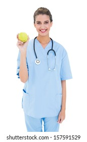 Pleased brown haired nurse in blue scrubs holding a green apple on white background