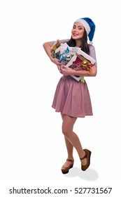 Pleased brunette with her presents looks right in the camera with positive emotions. She holds gift boxes with sweets. Isolated.