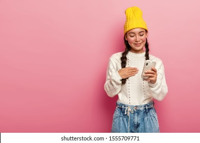 Pleased brunette Korean girl blogger texts sms during messaging with followers, edits media file, uses smartphone application, keeps hand on chest, touched to receive invitation to meet from friend
