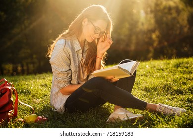 Pleased brunette woman in eyeglasses sitting on grass in park and reading book