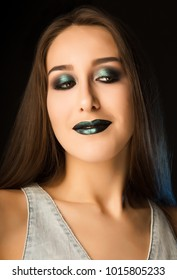 Pleased brunette woman with perfect skin and creative metallic green makeup. Closeup portrait at studio on a dark background