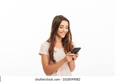 Pleased brunette woman in t-shirt writing message on smartphone over white background