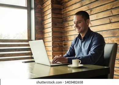 Pleased businessman or entrepreneur with a happy smile sitting working at a laptop computer in his office at a desk with cup of coffee