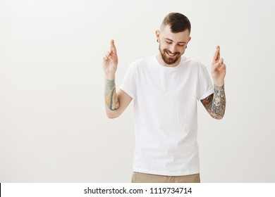 Pleased charming man with beard and tattoos on arms, looking down while smiling broadly and crossing index fingers, wishing for good luck and being assured in positive reply from girlfriend, wishing