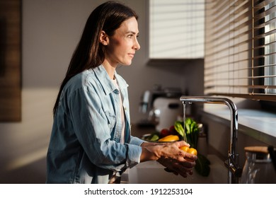 Pleased charming woman washing vegetables at home kitchen