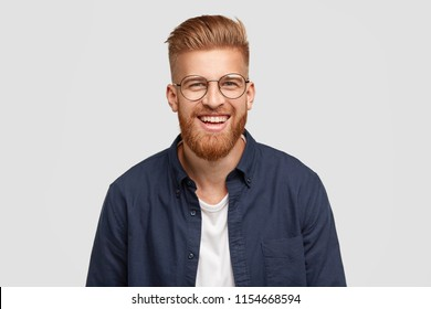 Pleased cheerful redhaired male with pleasant smile, giggles joyfully, spends free time with girlfriend, being in high spirit, shows white teeth, happy to have romantic relationships, stands in studio
