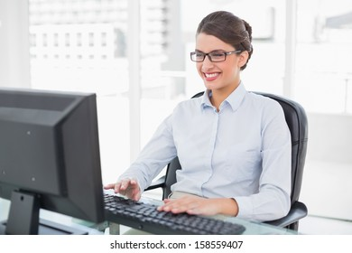 Pleased classy brown haired businesswoman using a computer in bright office