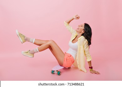 Pleased dark-haired girl in cute shorts and colorful socks playfully posing on skateboard. Indoor portrait of tanned young woman in bright accessories sitting on pink background and laughing.