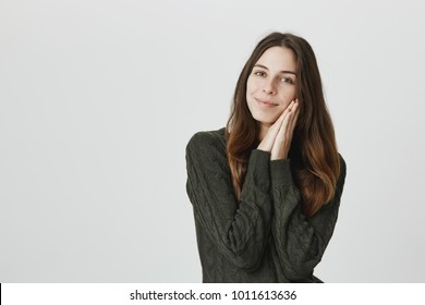 Pleased delightful dark haired smiling female, has dreamy expression, smiles, wears sweater, isolated against gray background. Attractive positive woman presses palms together in pleasure