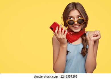 Pleased delightful female wears trendy shades, holds mobile phone, listens pleasant melody, enjoys high speed internet, waits for important call, isolated over yellow background with copy space