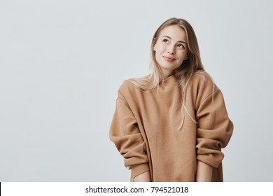 Pleased delightful smiling female with blonde dyed hair, has dreamy expression, wears cozy sweater, isolated against gray background. Attractive positive woman dreamily looks upwards