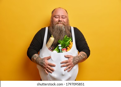 Pleased fatso keeps hands on stomach, buys junk food from supermarket, eats unhealthy products, doesnt care about weight, has satisfied expression, keeps eyes closed, poses indoor, yellow background
