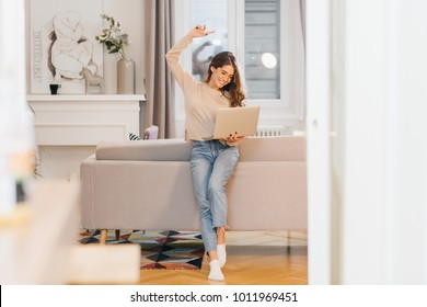 Pleased female freelancer happy for successful project. Enthusiastic lady in vintage jeans holding laptop, standing near sofa.