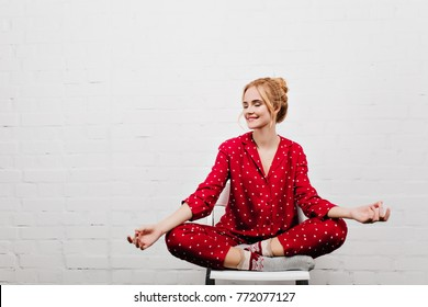 Pleased girl in red pajamas doing yoga on white background. Indoor portrait of blonde young lady sitting in lotus pose on chair.