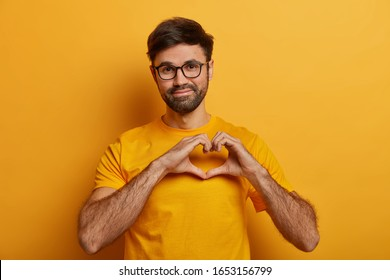 Pleased good looking man with thick bristle, shapes heart over chest, confesses in love, has romantic mood, expresses truthful feelings, wears yellow t shirt. My heart completely belongs to you