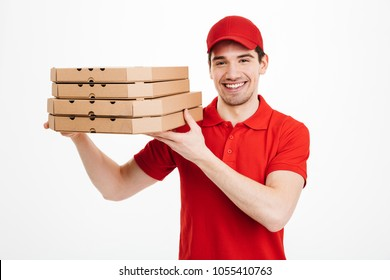 Pleased guy dealer in red t-shirt and cap working in delivery service and holding stack of pizza boxes isolated over white background
