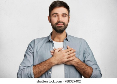 Pleased handsome male expresses his positive feeling to people who surround him, keeps hand on chest or heart, isolated over white concrete wall. Kind friendly looking unshaven man poses indoor