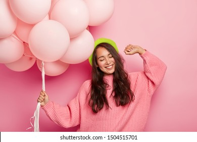 Pleased happy woman dances in rhythm of music, holds bunch of balloons, keeps eyes shut, feels joyous, has long hair, wears green beret and pink knitted sweater, isolated over rosy studio wall