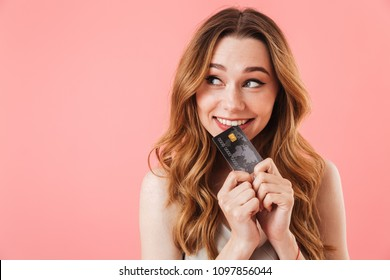 Pleased intrigued brunette woman in dress holding credit card and looking away over pink background