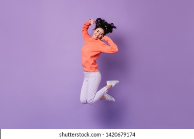 Pleased japanese girl jumping on purple background. Studio shot of blissful asian young woman.