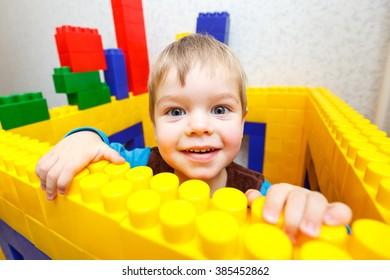 Pleased kid boy playing toy blocks