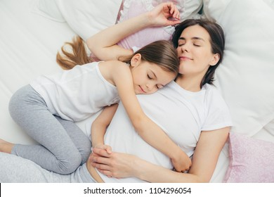 Pleased little child sleeps near her mother, embraces with love, has pleasant dreams, lie on comfortable bed. Mum and cute daughter have good sleep in bedroom. Family, sleeping and rest concept
