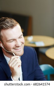 Pleased man listening to his favorite music in earphones