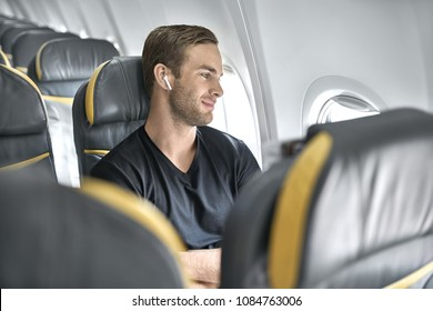 Pleased man sits in the airplane next to the window on the background of the empty seats. He wears a black T-shirt and wireless headphones and looks in the window with a smile. Closeup. Horizontal.