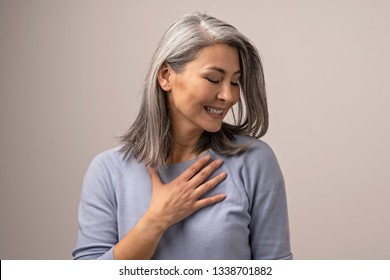 Pleased Middle-Aged Asian Woman Touches Her Chest Thanking. Smiling Woman Touching Her Chest With Hand And Looking Aside While Being Pleased. Portrait. Gratitude Concept