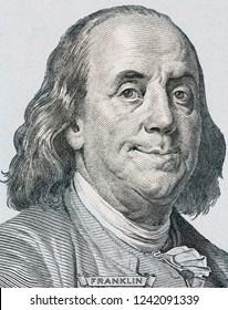 Pleased President Benjamin Franklin portrait on new one hundred US dollars banknote. Vertical close up portrait.