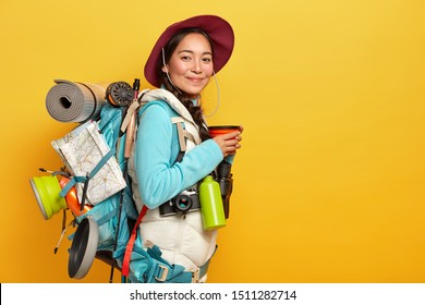 Pleased young Asian female traveler stops on her way to have coffee break, wears hat and casual outfit, poses with rucksack, has long trip, explores new places, likes travelling, isolated on yellow