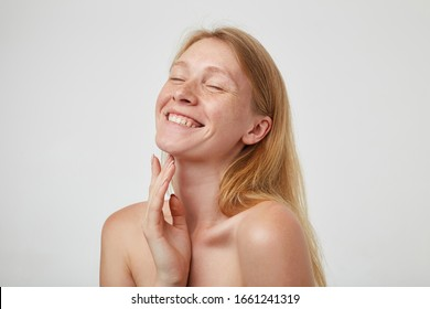 Pleased young good looking redhead female with natural makeup smiling cheerfully with closed eyes and touching her neck with raised hand, standing over white background