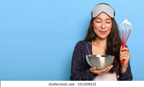 Pleased young housewife learns how to cook, watches culinary show and tries to make same dish, whisks cream in bowl with whisk, mixes ingredients for dough, wears casual domestic sleep costume