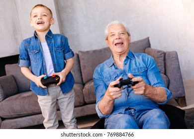 Pleasurable entertainment. Happy cheerful positive grandfather smiling and holding a game console while playing video games with his grandson