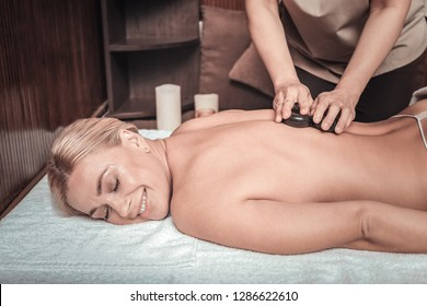 Pleasurable procedure. Delighted happy woman smiling while enjoying the stone massage