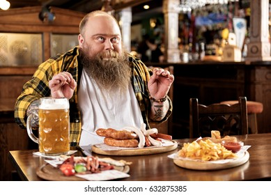 Pleasure bearded man eating food in boozer