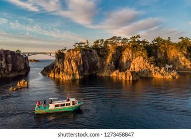 Pleasure boat sailing at Senkakuwan Bay marine park at sunset.
