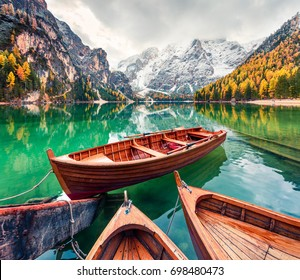 Pleasure boats on Braies Lakeand Seekofel mount on background. Colorful autumn morning in Italian Alps, Naturpark Fanes-Sennes-Prags, Dolomite, Italy, Europe. Traveling concept background.