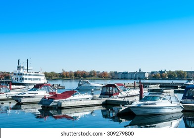 Pleasure boats and passengers boat with reflections on water anchored on Ontario lake Kingston Ontario Canada