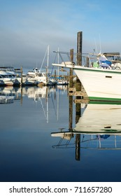 Pleasure boats with reflections in calm waters of Des Moines Marina, Des Moines, Washington