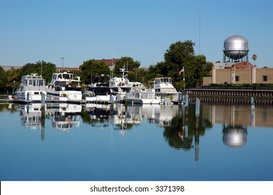 Pleasure Boats, Silver Water Tower, and Cityscape Reflected in Still River, Stocton California