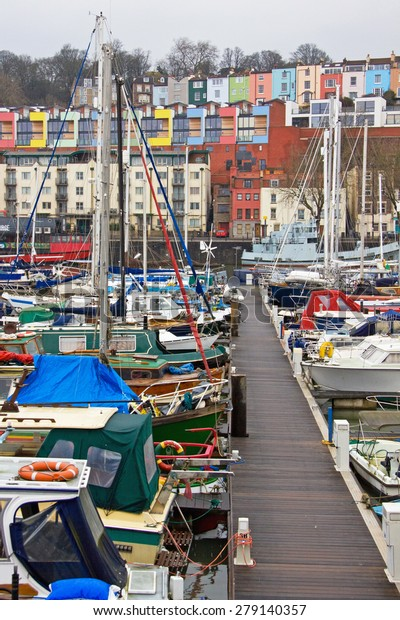 Pleasure craft moored in winter in Bristol harbour UK, overlooked by some of the city's more colorful housing