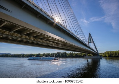 Pleasure cruise ship passing under Megyeri Bridge spanning over River Danube by Budapest, Hungary, seen from below