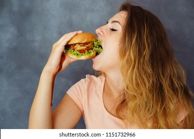 Pleasure, delight, enjoyment, treat, happiness, appetite, fast food. Cute young woman eating greedily delicious burger smearing hands with sauce