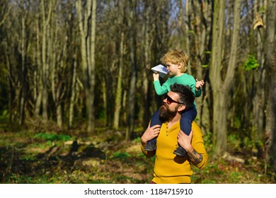 Pleasure is a path to joy. Father give little child piggybacking in pleasure park. Father and son spend time together.