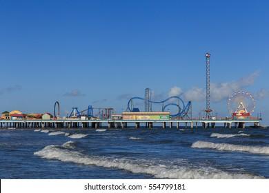 Pleasure Pier from the water/ Galveston Island Pleasure Pier/ The Pleasure Pier rides reaching out over the water on Galveston, Texas, USA.
