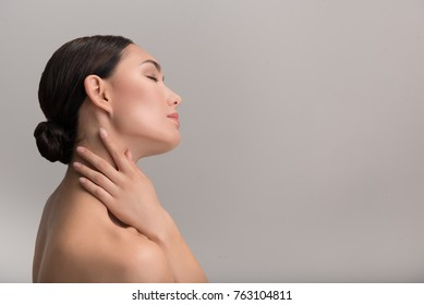 Pleasure. Side view profile of charming young naked woman is touching her naked while feeling pleasure from her soft skin. She is standing with closed eyes. Isolated background with copy space