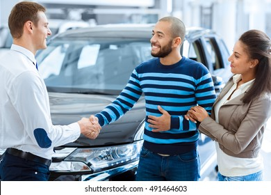 Pleasure working with you. Beautiful happy African couple embracing at the dealership after buying a new car together handsome man shaking hands with a salesman