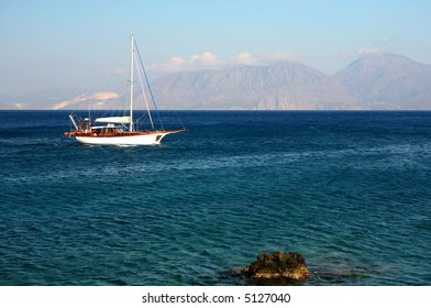 A pleasure yacht sailing off the shore of eastern Crete