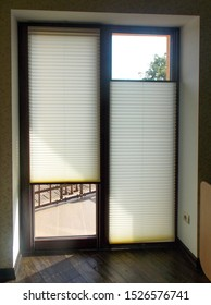 Pleated blinds closeup on the balcony door in a private house.  Modern top down bottom up privacy cellular shades on apartment window. Cordless pleated shades.